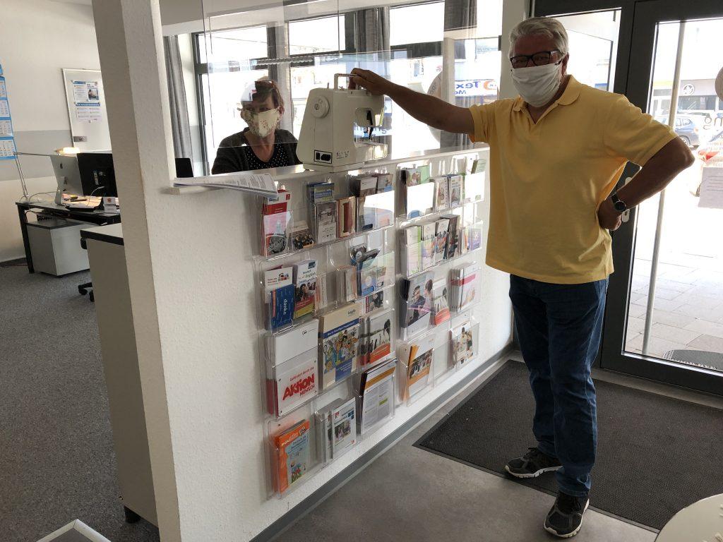 Nähmaschinen - Rainer Brunke steht vorne und hat eine gespendete Nähmaschine mitgebracht. Darmar Großkopf von der Freiwilligenagentur steht hinter der Scheibe und bedankt sich dafür.