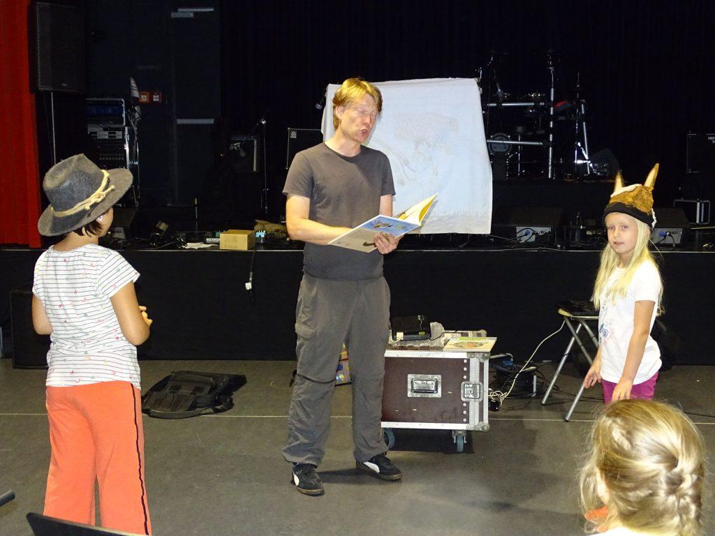 Kreativ-Tage im KufAHaus - Mann spielt mit verkleideten Kinder Theater und liest aus einem Buch