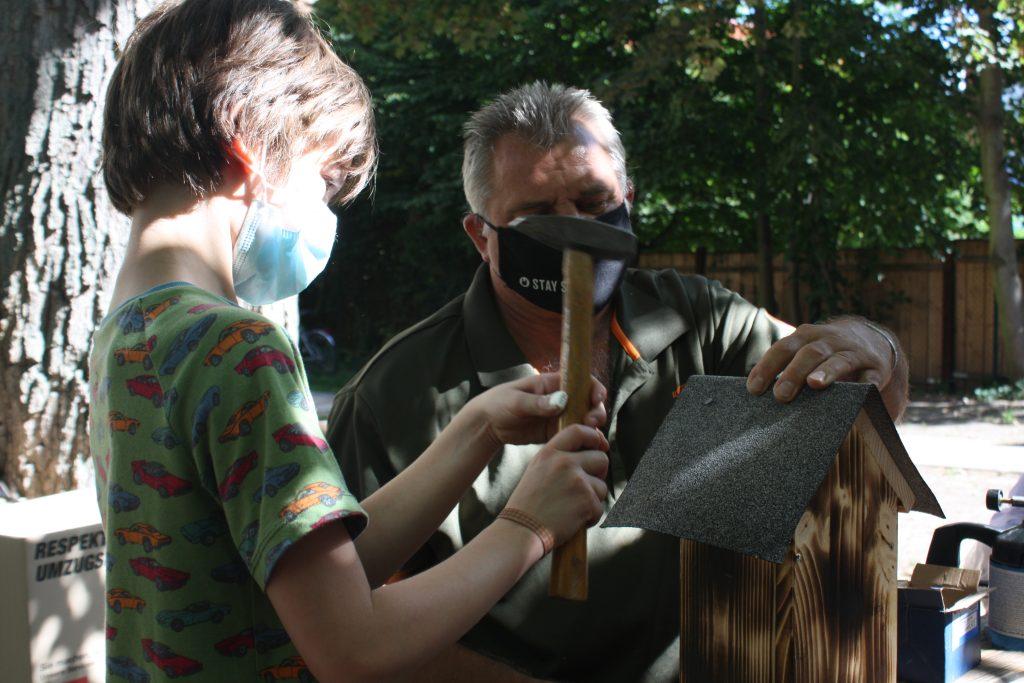 Mann und Junge bauen Bienen-Hotel