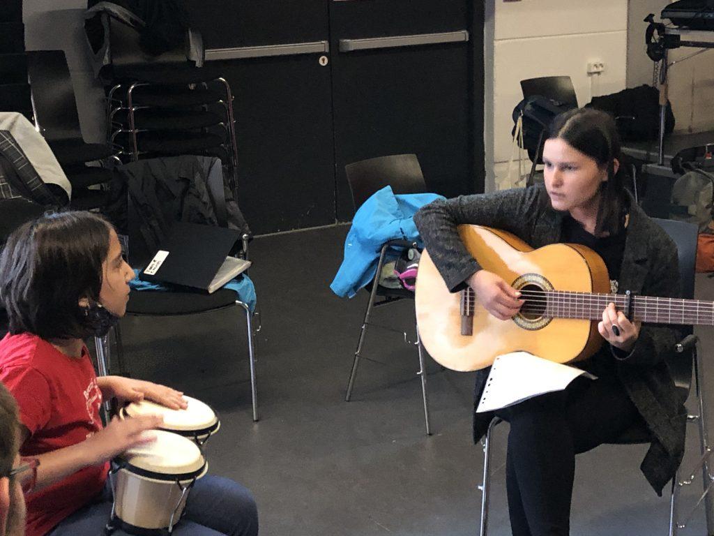 Junge Frau mit Gitarre musiziert mit Mädchen.