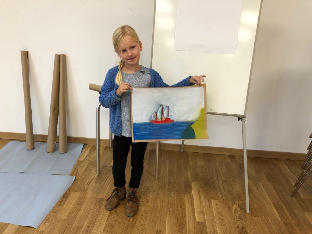 Ferienprogramm: Es wurde viel mit Kreide gemalt. Mädchen zeigt ein gemaltes Bild mit Wasser und Boot