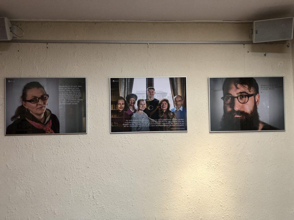 Ausstellung im Onkel Emma: Gesichter der Demokratie. Hier hängen drei Fotos der Ausstellung in den Räumen von Onkel Emma. Sie zeigen eine Frau, eine Gruppe und einen Mann mit Bart.