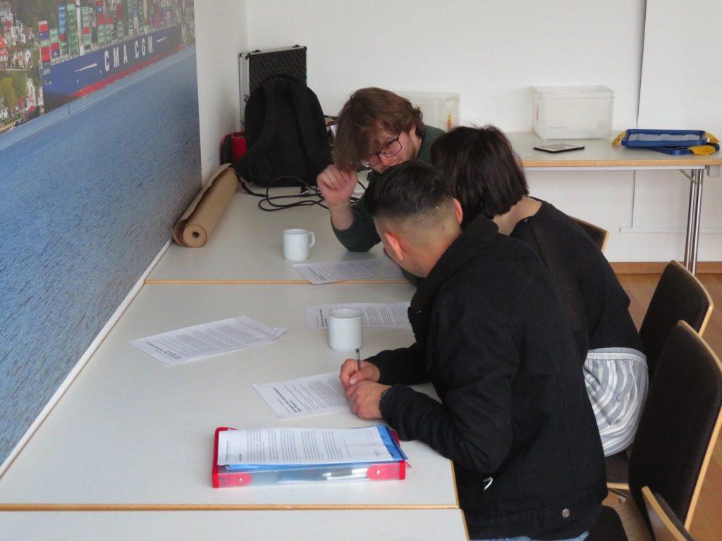 Drei junge Leute stecken die Köpfe zusammen bei einem Workshop in Hamburg (Archivfoto 2018)
