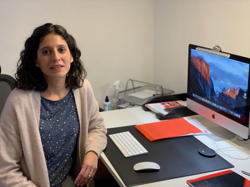 Tatiana Perez-Aristi macht Online-Meetings mit Frauen in Wolfenbüttel. Junge Frau sitzt vor einem Computer udn schaut den Betrachter an. Vor ihr die Computer-Maus, die Tastatur und der Bildschirm