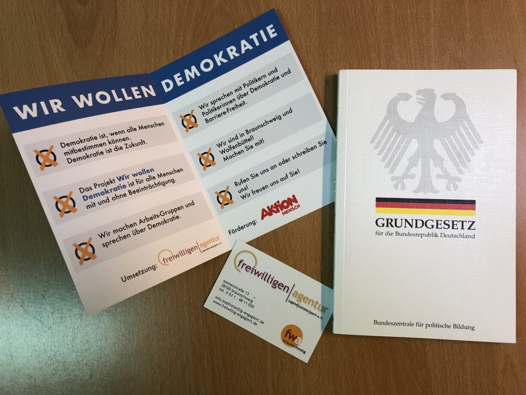 """Der Flyer des Projektes """"Wir wollen Demokratie ist aufgeschlagen. er erklärt in einfacher Sprache das Projekt. Rechts daneben ist ein Exemplar des Grundgesetzes. Unten eine Visitenkarte der Freiwilligenagentur."""