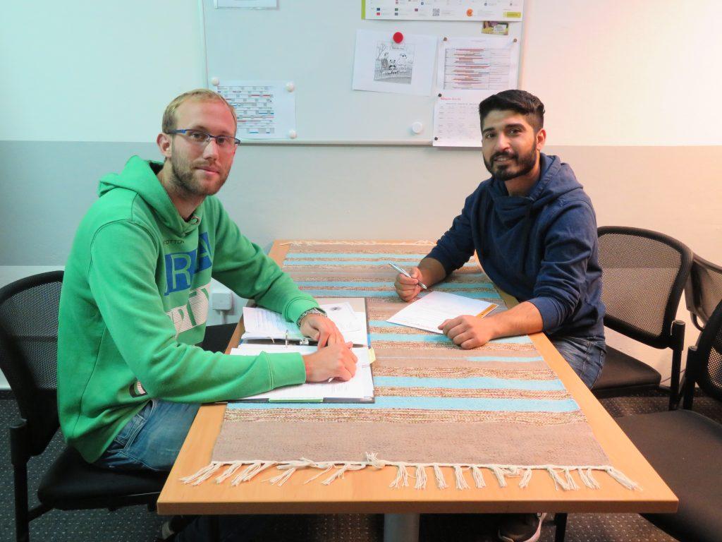 Man sieht zwei Männer mit Papieren und Stiften an einem Tisch sitzen: Mark Gindera berät Teilnehmerinnen und Teilnehmer für das Programm Chancenpatenschaften (das Foto wurde vor der Pandemie aufgenommen!)
